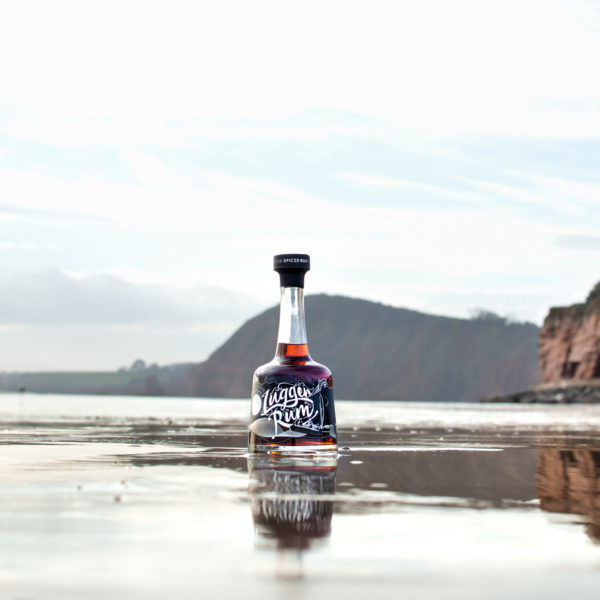 Lugger Rum on sand with Lyme Bay coast in the background